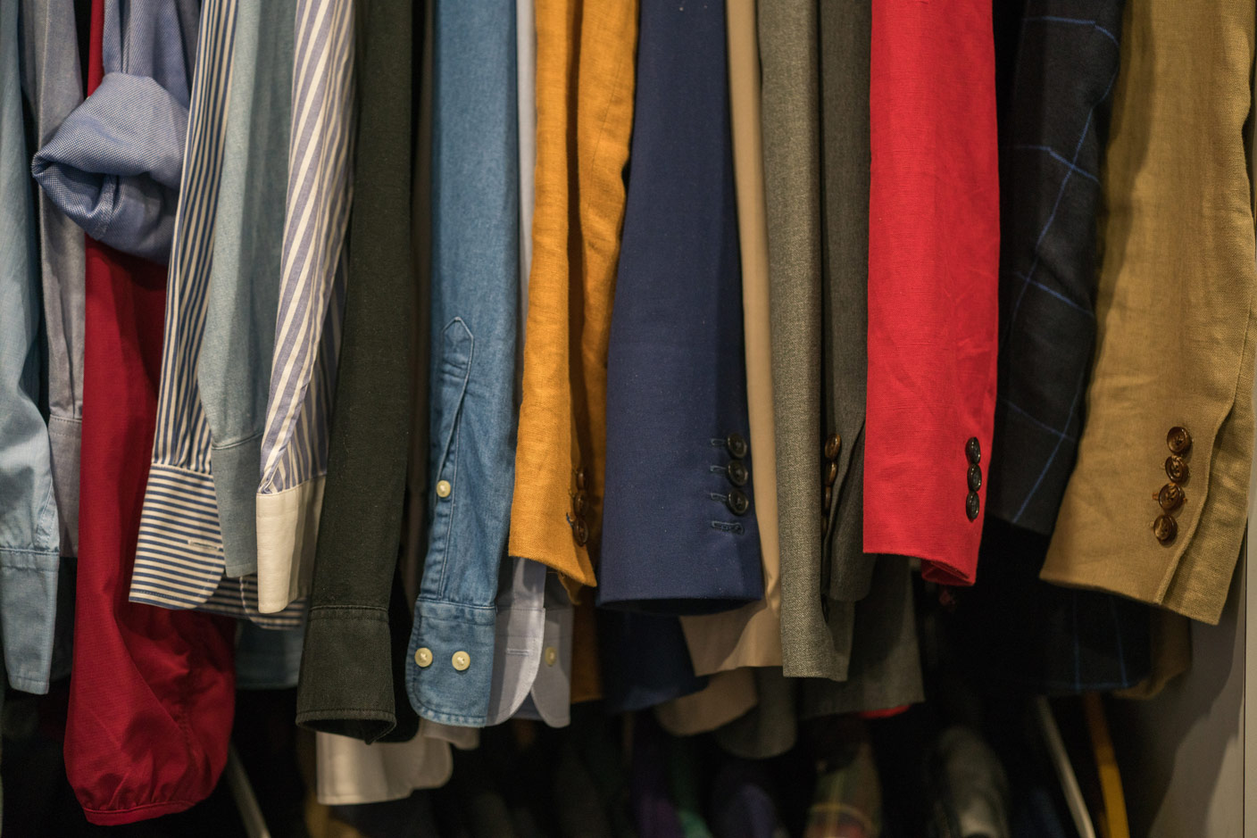 The picture shows clothes on hangers in a second-hand store